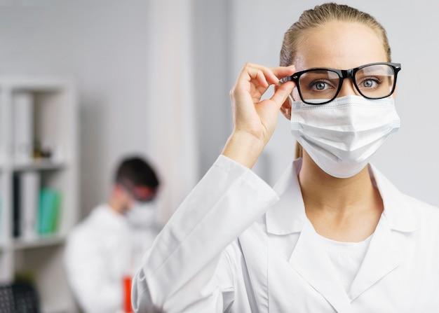 Retrato de mujer científica en el laboratorio con máscara médica