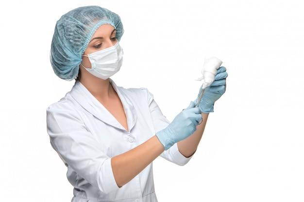 Retrato de mujer cirujano sosteniendo un instrumento quirúrgico sobre fondo blanco.
