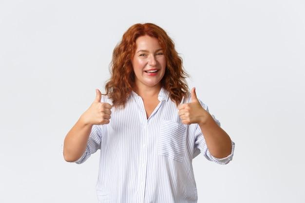 Retrato de mujer complacida mostrando pulgar hacia arriba en aprobación, como producto, garantía de calidad