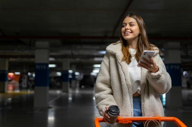 Retrato de mujer comprador con carrito de compras