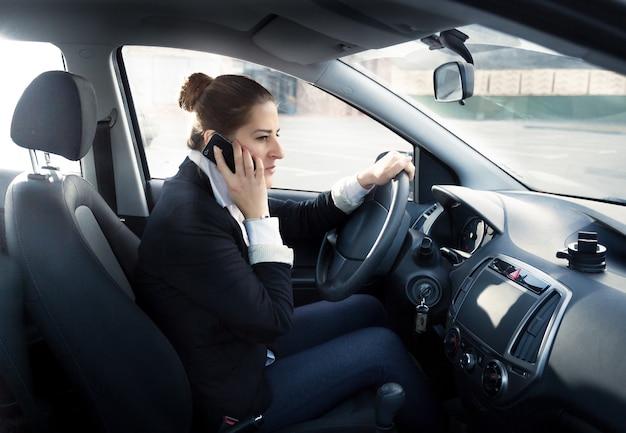 Retrato de mujer concentrada hablando por teléfono y conduciendo coche