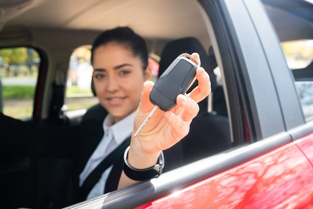 Retrato de mujer conductora profesional mostrando las llaves del coche