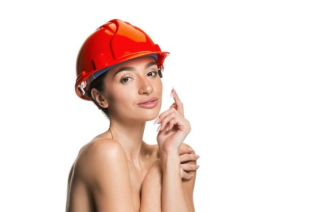 Retrato de mujer confiada feliz trabajador sonriente en casco naranja