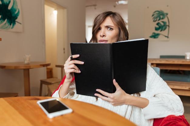 Retrato de una mujer confundida con bloc de notas de portada en blanco