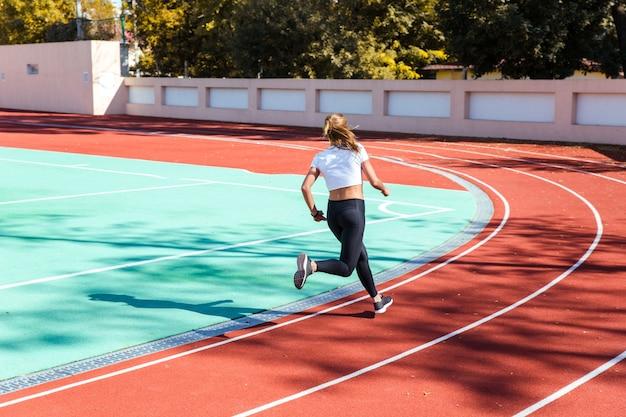 Retrato de una mujer corriendo en el estadio