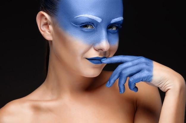 Retrato de una mujer cubierta con maquillaje artístico azul