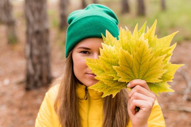 Retrato de mujer cubriéndose la cara con un montón de hojas de otoño