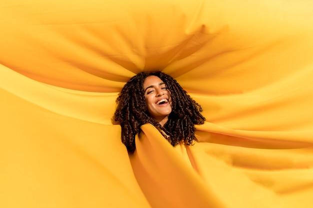 Retrato de mujer debajo de tela amarilla