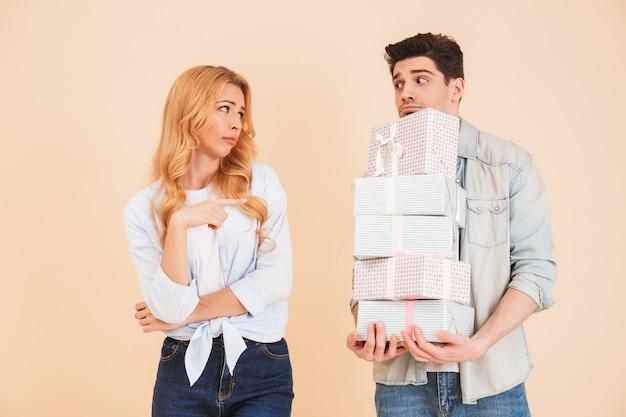 Retrato de mujer decepcionada que señala con el dedo al hombre molesto de pie con un montón de cajas de regalo, aislado sobre pared beige