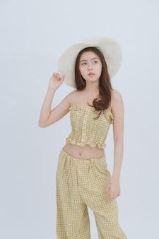 Retrato de la mujer delgada asiática que lleva el sombrero grande en el fondo aislado blanco.