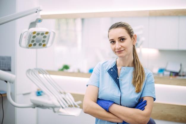 Retrato de mujer dentista. ella de pie en su consultorio.
