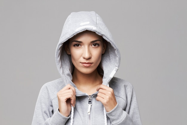 Retrato de mujer deportiva brutal en capucha y ropa deportiva en blanco.