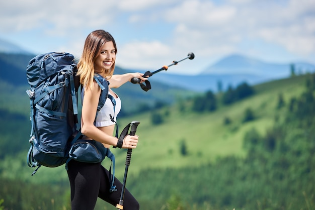 Retrato de mujer deportiva feliz turista con mochila azul apuntando lejos con sus bastones de trekking