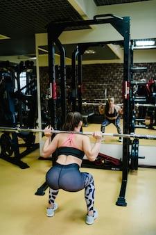 Retrato de mujer deportiva fuerte está haciendo ejercicio con barra en el gimnasio