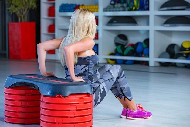 Retrato de mujer deportiva haciendo ejercicio físico en el gimnasio
