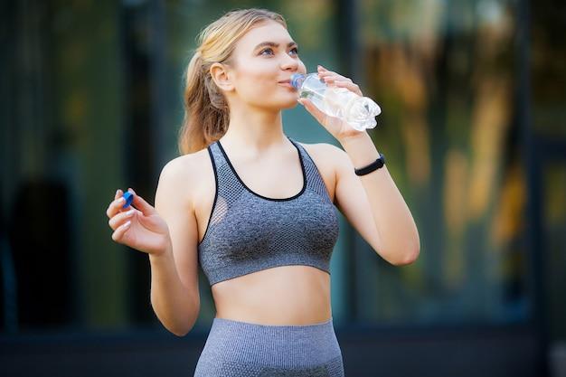 Retrato de una mujer deportiva en el parque con una pausa