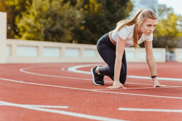 Retrato de una mujer deportiva en posición de estrella para correr en el estadio al aire libre