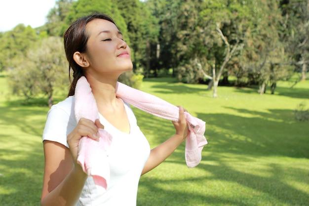 Retrato de mujer deportiva se siente relajada y feliz bajo el sol en el parque con aire fresco
