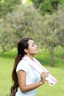 Retrato de mujer deportiva tomar una respiración profunda en el parque con aire fresco