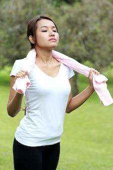 Retrato de mujer deportiva tomar un respiro mientras se estira con una toalla