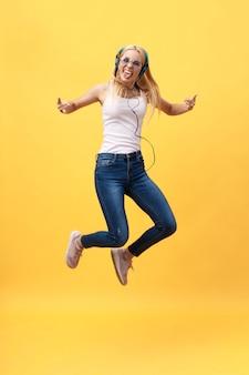 Retrato de mujer despreocupada en jean saltando mientras escucha música.