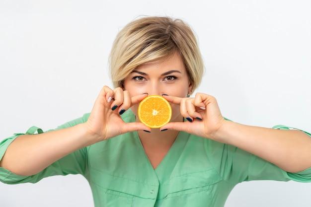 Retrato de mujer dietista sosteniendo y mostrando una rodaja de naranja sobre un fondo blanco.
