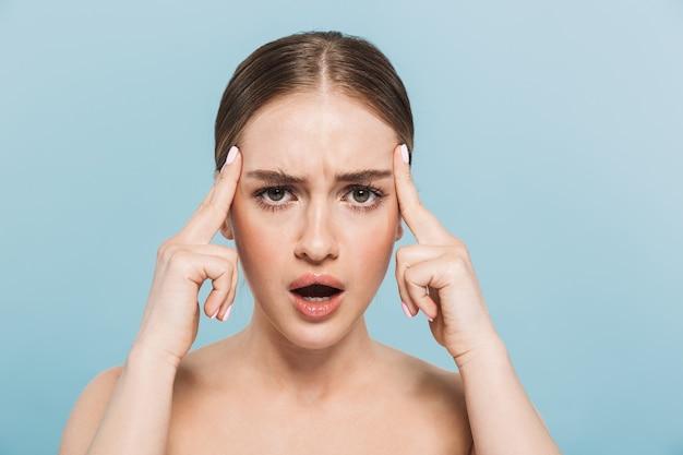 Retrato de una mujer disgustada bastante joven con dolor de cabeza posando aislada sobre pared azul.
