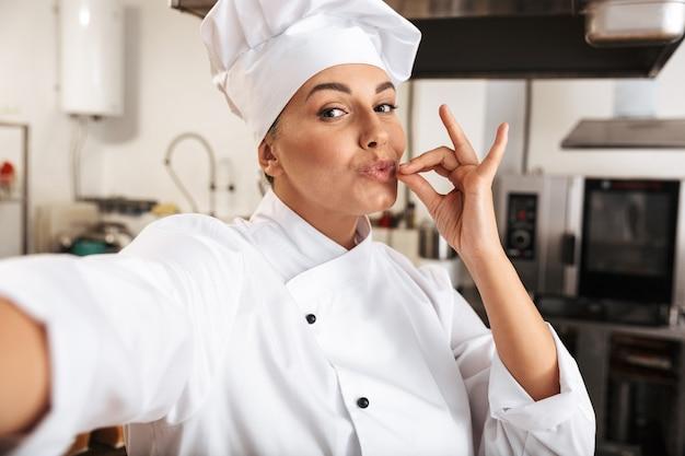 Retrato de mujer divertida chef vistiendo uniforme blanco, tomando selfie foto en la cocina del restaurante