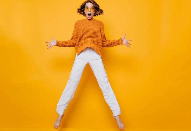 Retrato de mujer divertida en pantalones blancos jugando sobre fondo amarillo