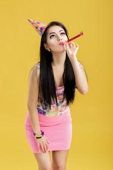 Retrato de mujer divertida con sombrero de cumpleaños y camisa rosa sobre amarillo