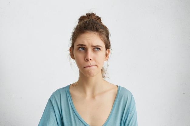 Retrato de mujer dudosa y pensativa mirando hacia arriba y curvando sus labios tratando de tomar una decisión. mujer irresoluta pensando en algo
