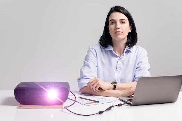 Retrato de mujer ejecutiva segura seria sentada a la mesa con laptop y papeles y viendo la presentación en la reunión
