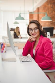 Retrato de mujer ejecutiva sonriente sentados frente al escritorio