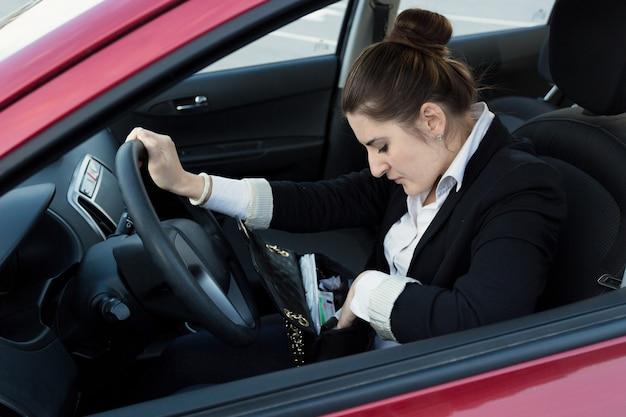 Retrato de mujer elegante conduciendo coche y mirando dentro del bolso