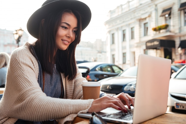 Retrato de una mujer elegante escribiendo en la computadora portátil