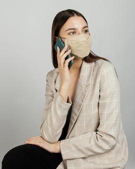 Retrato de mujer elegante con máscara con móvil