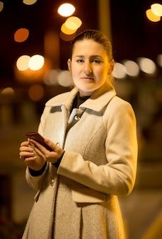 Retrato de mujer elegante posando con teléfono móvil en la calle por la noche
