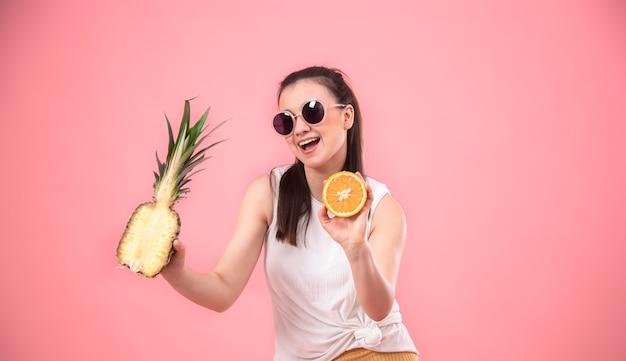 Retrato de una mujer elegante sobre un fondo rosa con frutas en sus manos. concepto de verano.