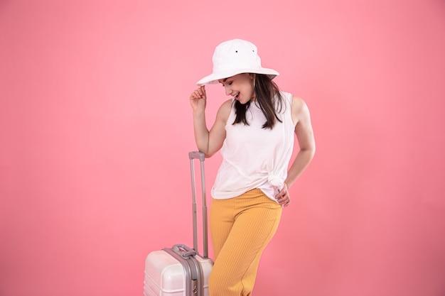 Retrato de una mujer elegante sobre un fondo rosa con una maleta para viajar.