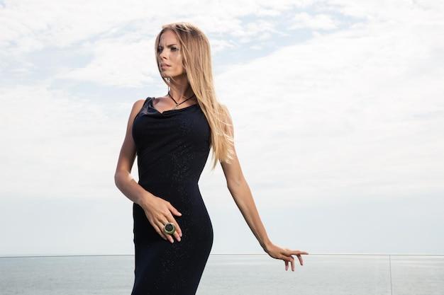 Retrato de una mujer elegante en vestido negro de pie al aire libre con el mar en la pared