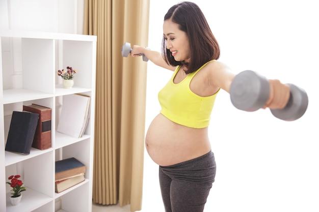 Retrato de mujer embarazada sana haciendo ejercicio con pesas en casa