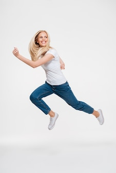 Retrato de una mujer emocionada feliz saltando
