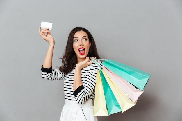 Retrato de una mujer emocionada mostrando tarjeta de crédito