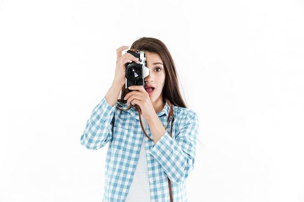 Retrato de una mujer emocionada tomando foto con cámara retro