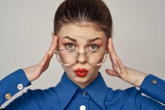 Retrato de mujer emocional en camisa azul y gafas modelo de maquillaje brillante fondo claro vista recortada espacio en blanco. foto de alta calidad