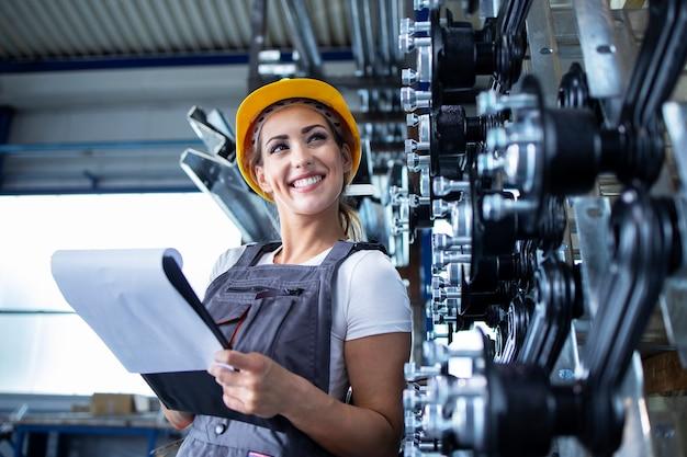 Retrato de mujer empleada industrial en uniforme de trabajo y casco comprobando la producción en la fábrica.