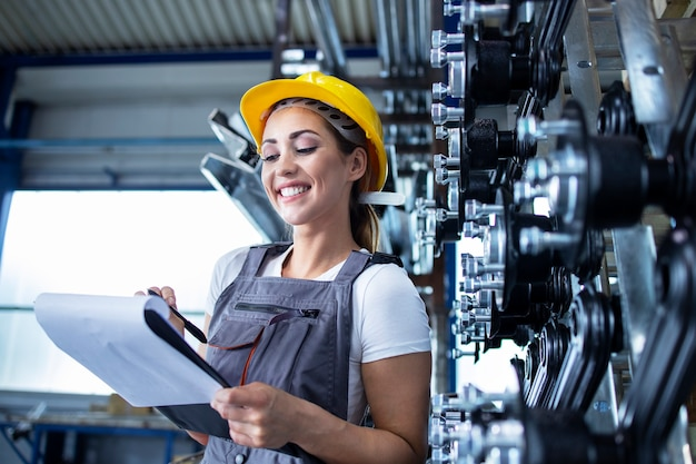 Retrato de mujer empleada industrial en uniforme de trabajo y casco escribiendo resultados de producción en fábrica