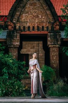 Retrato de mujer encantadora asiática con un hermoso vestido típico tailandés en el templo antiguo o lugar famoso con pose graciosamente