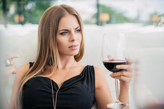 Retrato de una mujer encantadora bebiendo vino tinto en el restaurante