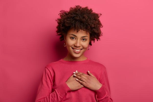 El retrato de una mujer encantadora conmovida toca el corazón, hace un signo de afecto y gratitud, tiene una sonrisa amable, usa un jersey carmesí, aprecia las palabras bonitas